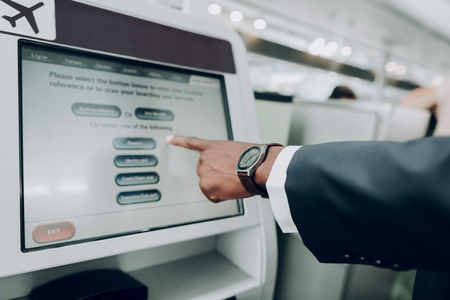 Tap here. Close up of male hand is pointing on the screen of information terminal inside
