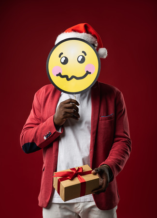 I am shy. Man in santa hat covering face with emoji on red background. Lovely gift box with ribbon and bow in gentleman hand. Isolated on red background