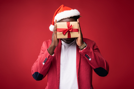 Can you see me. Young man in santa hat hiding face under gift box with red ribbon. Isolated on red background