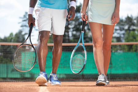 Close up of male and female legs while playing tennis in open air. Couple is walking along playground during break. They are holding rackets Stok Fotoğraf
