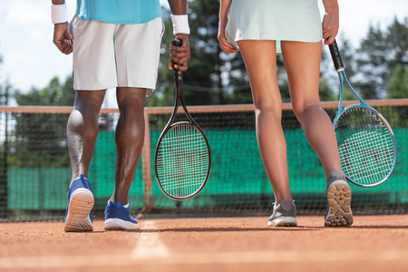 Close up of male and female sports people legs while playing active game. They are standing on court with focus on back and holding rackets. Team mates are preparing for match Stockfoto