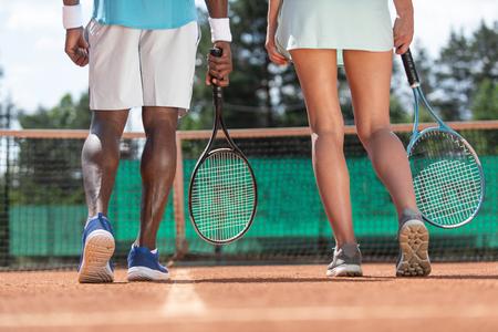 Gros plan des jambes de sportifs masculins et féminins tout en jouant au jeu actif. Ils sont debout sur le court avec un accent sur le dos et tenant des raquettes. Les coéquipiers se préparent pour le match