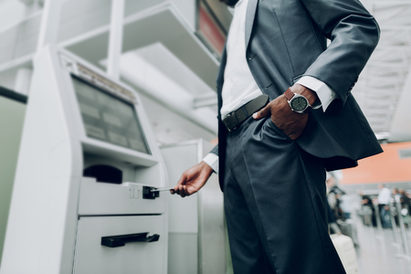 Close up of male is holding hand with watch in his pocket, while standing near cash dispenser 版權商用圖片