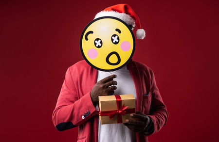 I am hiding. Man in santa hat covering face with emoji and demonstrating gift box with ribbon. Isolated on red background