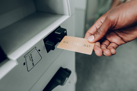 Close up of male hand is picking up bank gold card from cash machine