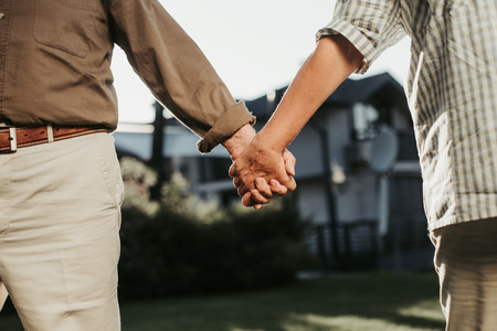 Close up of female hand is kept close to man figure. Twosome standing on lawn fronting house at blurred background