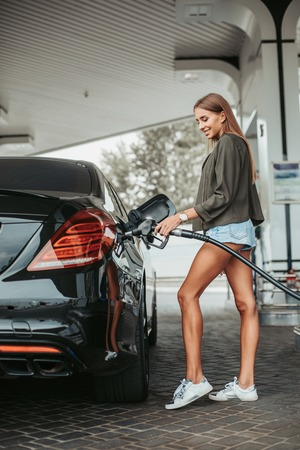 Full length side view beaming female refueling the contemporary automobile while standing near it and keeping hose in hands outside
