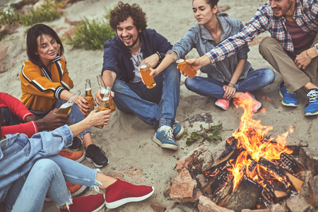Have a toast. Top view of group of cheerful friends sitting on the beach around campfire and drinking beer Banco de Imagens