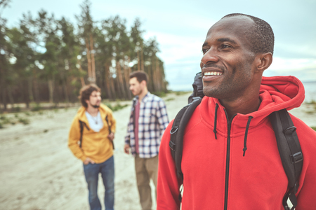 Travelling newer alone. Waist up portrait of man having stroll along seaside with friends Stock Photo