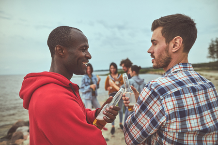 Waist up portrait of two smile man having conversation and drinking beer during party at the seaside