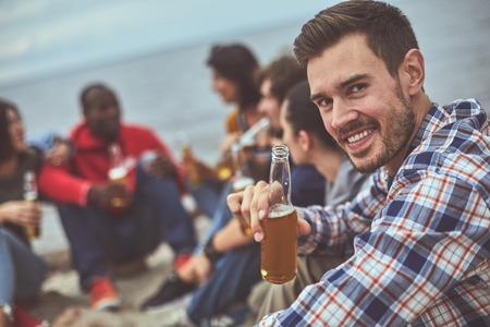 Cheers. Portrait of guy holding glass of beer in his hand and spending time with friends Banco de Imagens