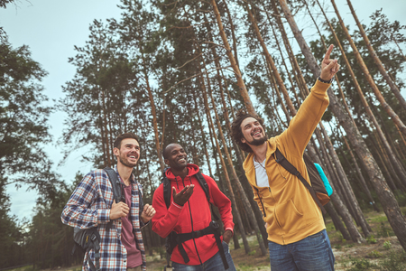 Stay in forest. Portrait of young man pointing best direction on their track for friends and smiling