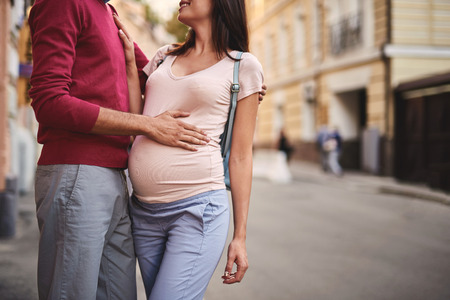 Tender moment. Cropped portrait of young bearded man hugging his beautiful pregnant wife and touching her belly. Smiling lady placing hand on husband chest