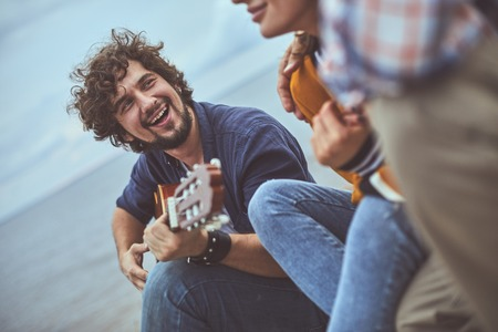 Heartwarming melody. Portrait of musician singing a song to his friends while playing the guitar Stok Fotoğraf