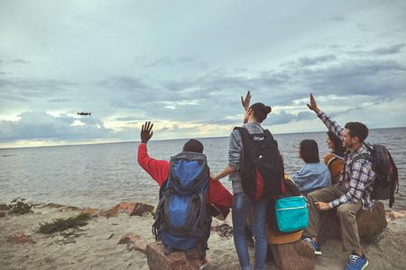 Agitando le mani. Gruppo di persone sedute in riva al mare e agitando la mano per una foto comune su quadricottero