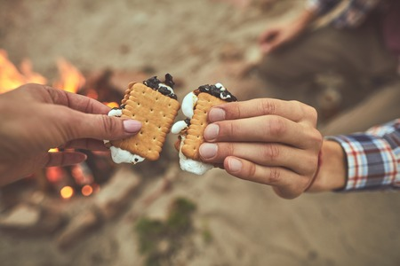 Bite and sup. Close up of people hands holding sweet cookies at the beach Stock Photo