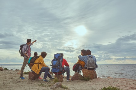 Moment of placidity. Portrait of group of travelers sitting at seashore and contemplating splendid landscape Stock Photo