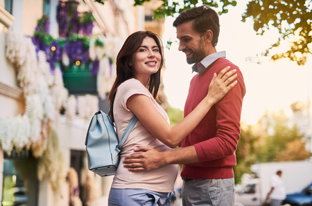 Unforgettable moment with you. Waist up portrait of charming pregnant woman in husband arms looking away and smiling. Bearded gentleman staring at lady with happy expression 写真素材