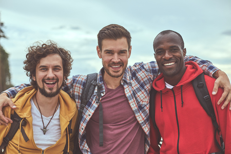 Diverse but together. Waist up portrait of positive guys making friendly embrace and smiling in front of camera Stock Photo