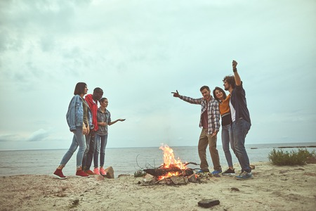 Get together. Happy friends standing near bonfire while telling stories each other at the sea shore Banco de Imagens