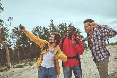 Say cheese. Happy travelers making selfie picture on the shore with forest on background
