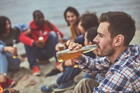 On same wave. Portrait of young guy drinking beer from glass bottle with his friends on background