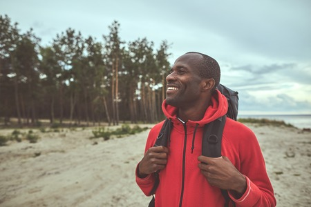 Enjoying nature. Waist up portrait of man standing on the shore and looking at the forest. He holding his backpack with both hand. Copy space on the left side