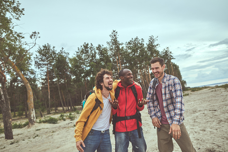 Hilarious journey. Three young guys laughing out loud during stroll at the seaside near pine forest Stock Photo