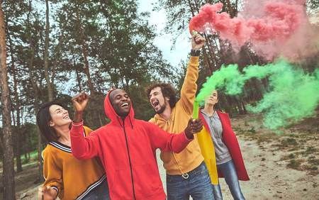 Colorful life. Happy friends fooling around in the woods while using colorful smoke pelletes and smiling Stock Photo