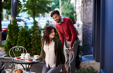 Tender love and care. Portrait of beautiful young couple having romantic date in outdoor cafe. Gentleman helping pregnant lady to sit down at the table Stock Photo