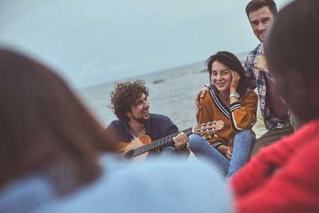 Singing and listening. Group of happy people sitting in circle while smile man jamming on the guitar