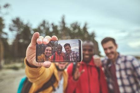 Photo to remember. Close up of male hand holding smartphone and making selfie with friends