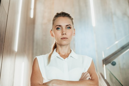 Portrait of serious strict pretty female employer with crossing hands on chest locating in vivid room Stock Photo