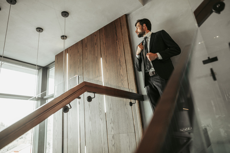 Side view calm unshaven male employee touching jacket of suit while looking away. He standing on stairs inside contemporary building