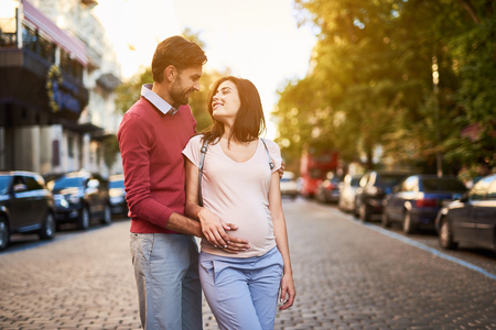 I adore you. Portrait of beautiful young couple looking at each other with love. They standing on sunny boulevard with cars Stok Fotoğraf
