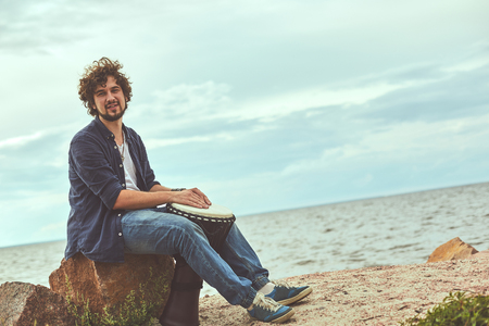 World music. Portrait of curly man sitting on the beach and playing ethic music on djembe. Copy space on the right side