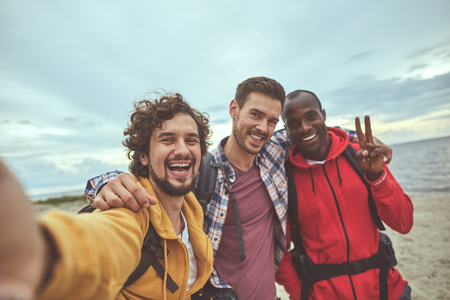 Unforgettable voyage. Waist up portrait of happy mates posing while make nice selfie on nature background