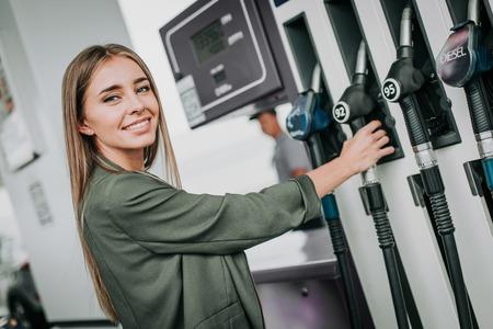 現代の車でガソリンを伐採するために腕にガソリンホースを保持している陽気な女の子の肖像画。彼女はカメラを見ている