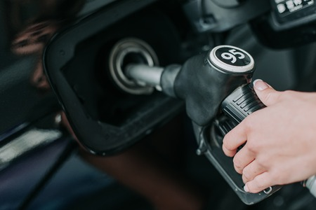 Close up woman hand holding petrol pump nozzle while servicing the contemporary vehicle outdoor