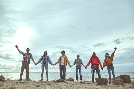 Gather together. Full length portrait of cheerful friends holding hands on the beach and smiling Banco de Imagens - 108584971