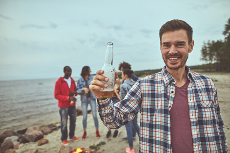 Portrait of smile man holding bottle of beer in hand. His friends standing on background near bonfire