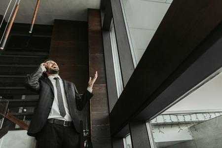 Portrait of laughing bearded male employer speaking on phone while gesticulating hand. He locating in hall during communication Imagens