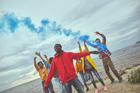 Playful mood. Group of friends standing on the beach and dancing while one of them setting blue smoke pellet