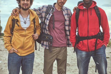 We are backpackers. Group portrait of three friends standing in front of camera while embracing Stock Photo