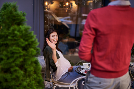 I was waiting for you. Smiling lovely woman touching belly and greeting young man. They having date at outdoor cafe