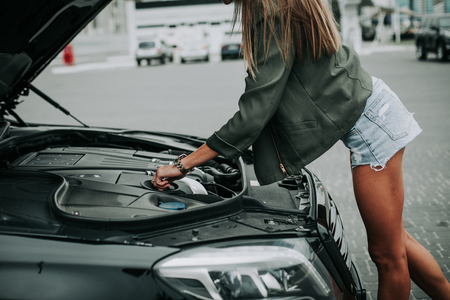 Young female taking engine of modern vehicle while standing opposite open hood outdoor