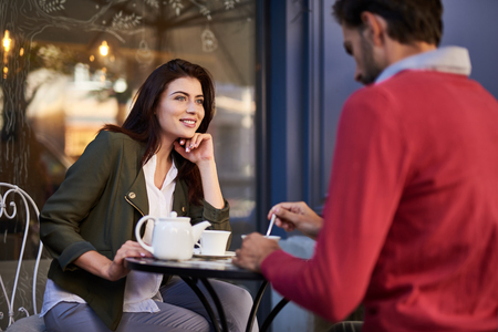 Happy being with you. Charming woman sitting at the table with cup of tea and looking at bearded man with smile Foto de archivo - 108585246
