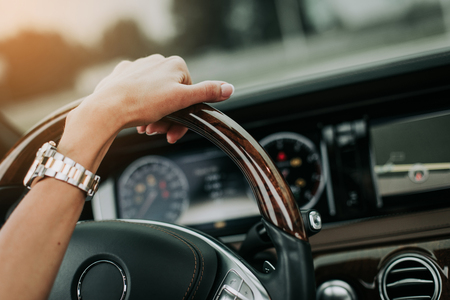 Close up female hand holding steering wheel while driving car. She wearing modern watch