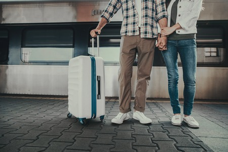 Female and man holding hands together while locating opposite train on platform before trip