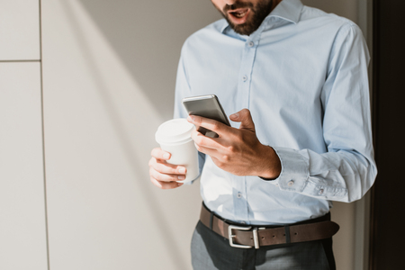 Amazed office worker is looking at mobile phone with open mouth. He is standing in light interior and holding cup of hot drink. Copy space in left side